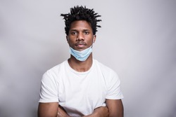 A portrait of an Afro-American young serious athletic young man in the white t-shirt, the crossed hands, and pulled down mask, serious, isolated on the grey background