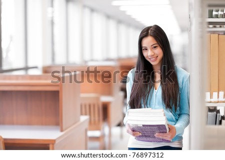 A portrait of an Asian college student holding books in the library