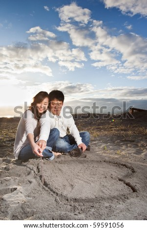 A portrait of an asian couple drawing love symbol on the sand