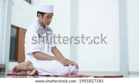 A portrait of an asian muslim man pray at mosque, the pray name is sholat, regards end of sholat Photo stock ©