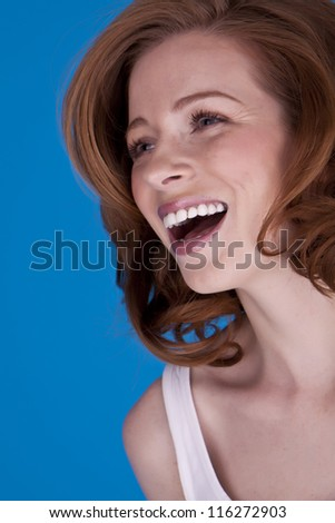 A portrait of an attractive woman with red hair on a blue background. Attractive woman.