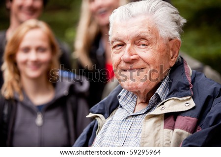 A portrait of an elderly man with young people in the background
