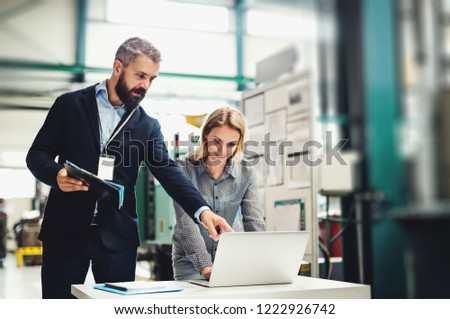 A portrait of an industrial man and woman engineer with laptop in a factory, working. #1222926742