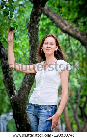 a portrait of attractive young woman  is in a park