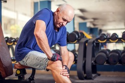 A portrait of bald senior man feeling strong knee pain during training in the gym. People, healthcare and lifestyle concept