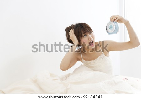 a portrait of beautiful asian woman looking at the clock on the bed