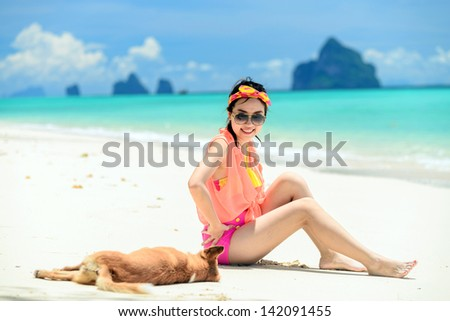 A portrait of beautiful asian woman on relaxing the beach with dog - stock photo
