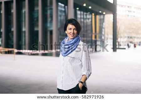 A portrait of beautiful caucasian female with short dark hairs wearing striped shirt and light blue scarf and smiling at the camera while standing on a blurred urban background. #582971926
