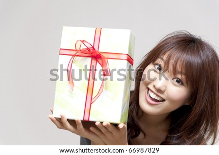 a portrait of beautiful girl holding a gift box isolated on white background