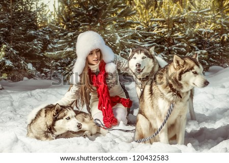 A portrait of beautiful woman with three dogs in the winter forest