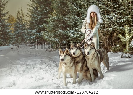 A portrait of beautiful woman with three dogs in winter forest