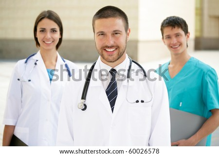 A portrait of doctor with two attractive colleagues in the background