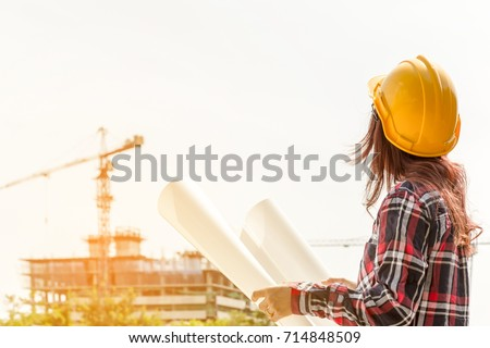 A portrait of engineer woman looking construction. Asian woman architect with blueprint in hand and yellow helmet with select focus and use effect filter. Concept Engineer and business work. #714848509