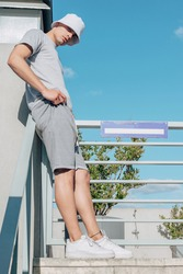 A portrait of fashionable latin man wearing a white bucket hat, grey t-shirt, grey shorts and white shoes outdoor. Mockup clothes.