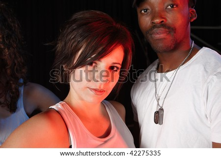 A portrait of female and male freestyle hip-hop dancers. Lit with spotlights