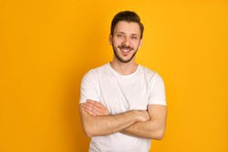 A portrait of handsome man in in white t-shirt crossing hands over yellow background, smiling happily, feeling attractive.