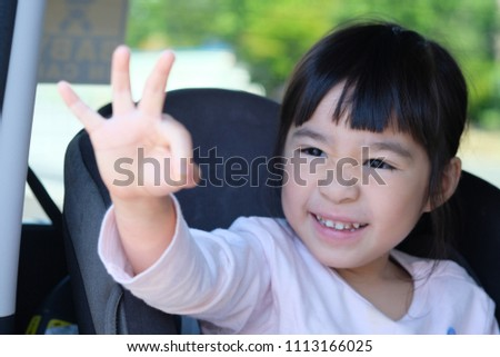 A portrait of lovely asian little smiling and making o.k. sign in the child seat