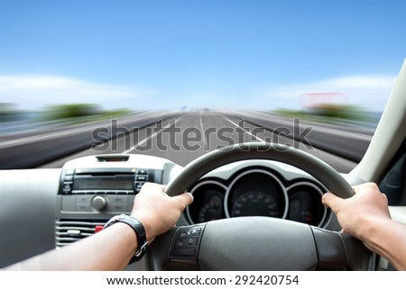 A portrait of Man's hand on steering wheel driving fast on the road