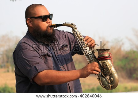 A portrait of saxophone player in the park