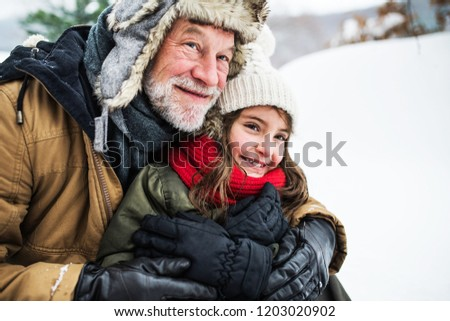 A portrait of senior grandfather and a small girl in snow on a winter day.