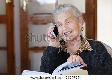 A portrait of senior woman using a cell phone - stock photo