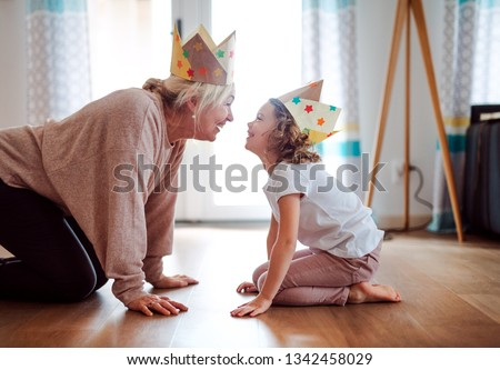 A portrait of small girl with grandmother having fun at home.