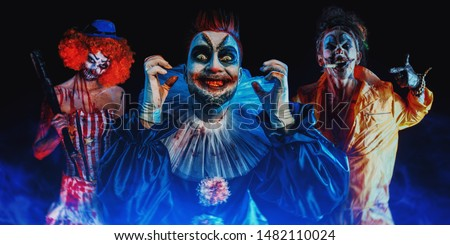 A portrait of three angry crazy clowns from a horror film. Halloween, carnival.