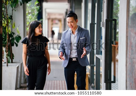 A portrait of two professional business people walking and talking. They are deep in conversation as they walk on a street in a city in Asia. The man and woman are both professionally dressed.