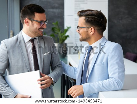 A portrait of two young smiling businessmen holding a tablet during a break  in the office. Business concept