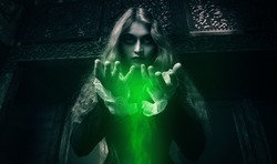 A portrait of witch holding green magic dust in his hands in an old wooden castle. Magic, dark force, spell.