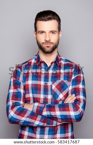 A portrait of young confident man in checkered shirt with crossed arms isolated on gray background