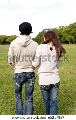 a portrait of young couple walking in the park