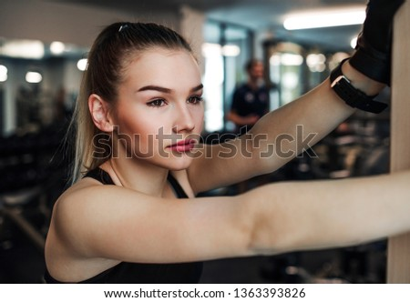 A portrait of young girl or woman standing in a gym. #1363393826