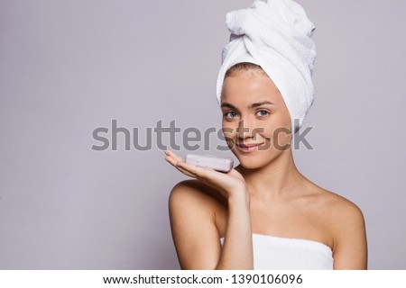 A portrait of young woman with a bar of soap in a studio, beauty and skin care.
