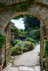 A portrait orientation photo of an Italian garden viewed through a gated arch in a stone wall, showing paving stones and a pathway through a lush garden with plants spilling onto the path.