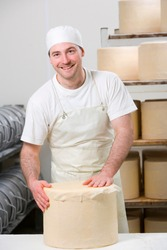 A portrait shot of a cheese maker smiling at camera while covering new farmhouse cheddar cheese wheel with a cheesecloth.