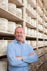 A portrait shot of a owner standing in a cellar and smiling with aged cheddar cheese wheels in background.
