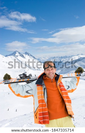 A portrait shot of a smiling man holding a snowboard over his shoulders on a snowy mountain.