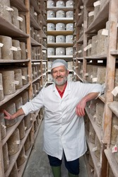 A portrait shot of a smiling senior cheese maker standing between the shelves of aged cheddar cheese wheels in a cellar.