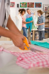 A portrait shot of a teacher talking to his students about clothing in a home economics classroom with a hand cutting fabric in foreground.