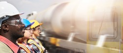 A portrait three-person team of petroleum depot engineers standing in line against the blurred background of a tanker train. The petroleum transportation industry by a rail system.