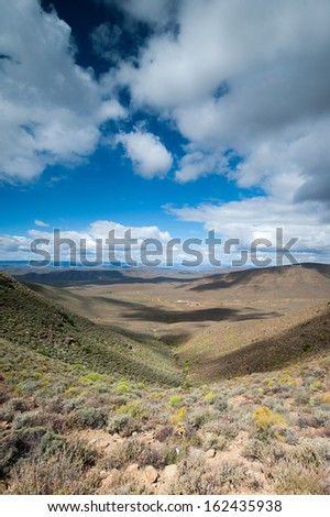 A portrait view of a semi arid landscape with clouds casting a shadow