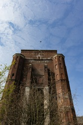 A portrait view of the old abandoned brick building with a bird flying over, at the Ewald mine in Herten, Germany, near Gladbeck, on a cloudy day.