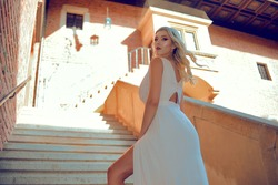 A posh woman in a long white dress climbs the steps to the castle. The blonde looks over her shoulder at the camera. model in a fairy tale