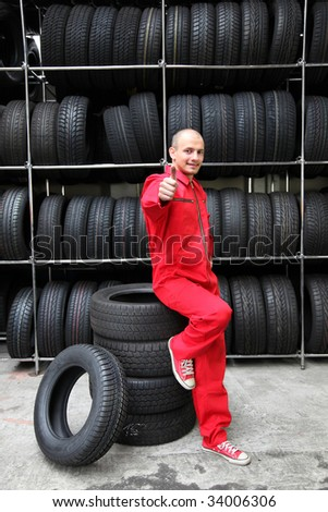 A positive mechanic in a garage standing next to a rack full of tires and making a positive gesture