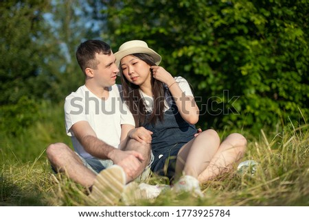 A positive young international couple in love while relaxing outdoors in a Park in the summer.