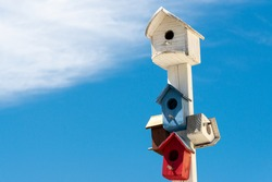 A post with a largely white color wooden birdhouse for birds. The house has a single round hole in the center. Below are multiple small birdhouses similar to the white but red, blue, and white in colo