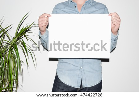 A3 Poster Mock-Up - Man in a denim shirt holding a poster on a white background. Hipster Aesthetic #474422728