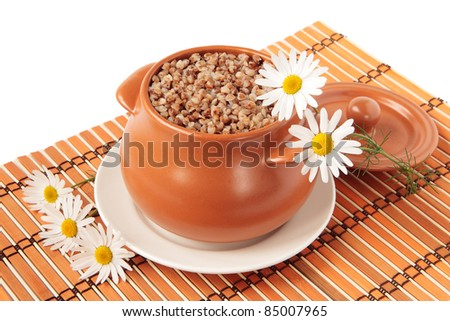 A pot of buckwheat porridge and five chamomiles on a bamboo napkin