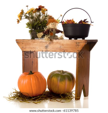 A pot of fall flowers, a tiny scarecrow, and a caudron full of leaves on an old wooden bench, with two pumpkins under it.  Isolated on white.